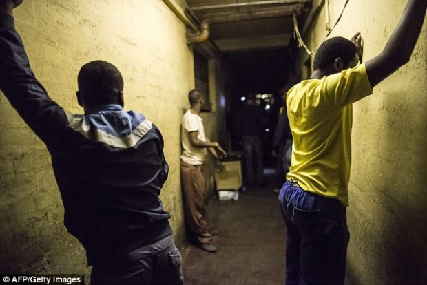 Hands up: Zulus up against a wall waiting to be searched during the police raid on the hostel last night