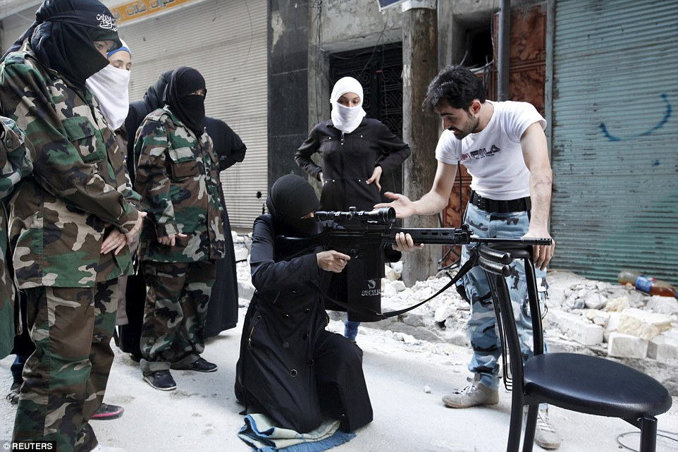 Line of fire: A female member of the 'Mother Aisha' battalion, an all-female rebel group in Syria, receives instruction as she holds a rifle during military training in Aleppo's Salaheddine district
