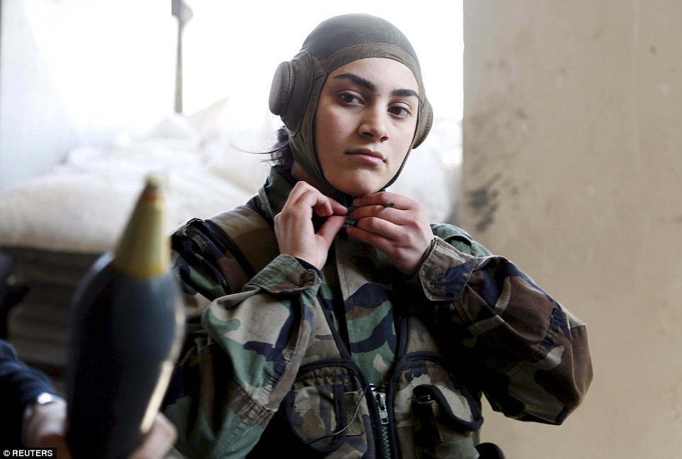 Protection: A member of a Female Commando Battalion - part of the Syrian Army - attaches her headgear in the government-controlled area of Jobar, a suburb of the capital Damascus in March