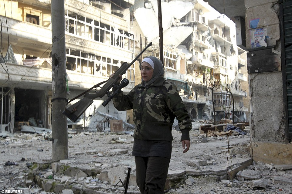 A Syrian Palestinian woman known only as 'Guevara' - married to an Al Wa'ad battalion commander - is pictured holding her gun and walking through the ruins of a street in the city of Aleppo, Syria