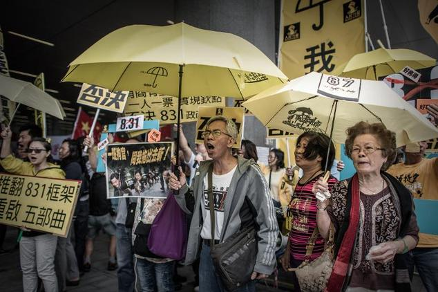 A pro-democracy demonstrators shout slogans during a protest outside the government building in Hong Kong on April 22, 2015