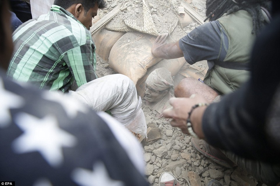 A man is buried up to his neck in rubble as the rescue teams attempt to dig him free from the collapsed building in the capital of Nepal