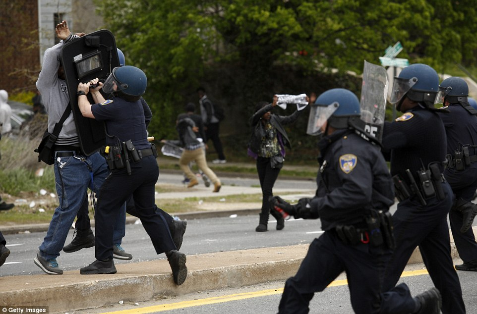 Rushed: A protestor is confronted by officers after huge riots broke out on the streets of Baltimore between hundreds of demonstrators and police on Monday