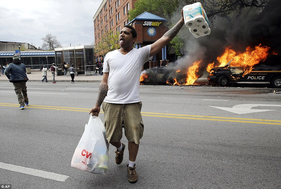 Looting: A man carries away what he appears to have stolen from a CBS pharmacy as two police cars burn behind him as Baltimore was set on fire by rioters on Monday afternoon