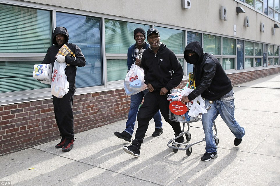 No laughing matter: Protesters who have looted a check-cashing business and other stores in Baltimore rush away with their haul using a trolley