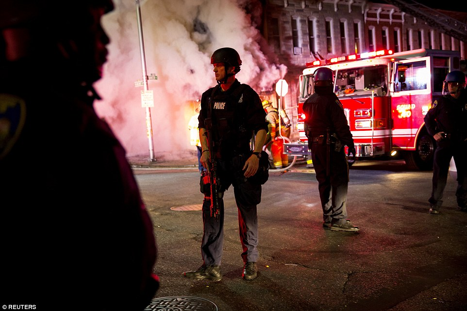 Police stand nearby as firefighters attack a fire in a convenience store and residence during clashes after the funeral of Freddie Gray