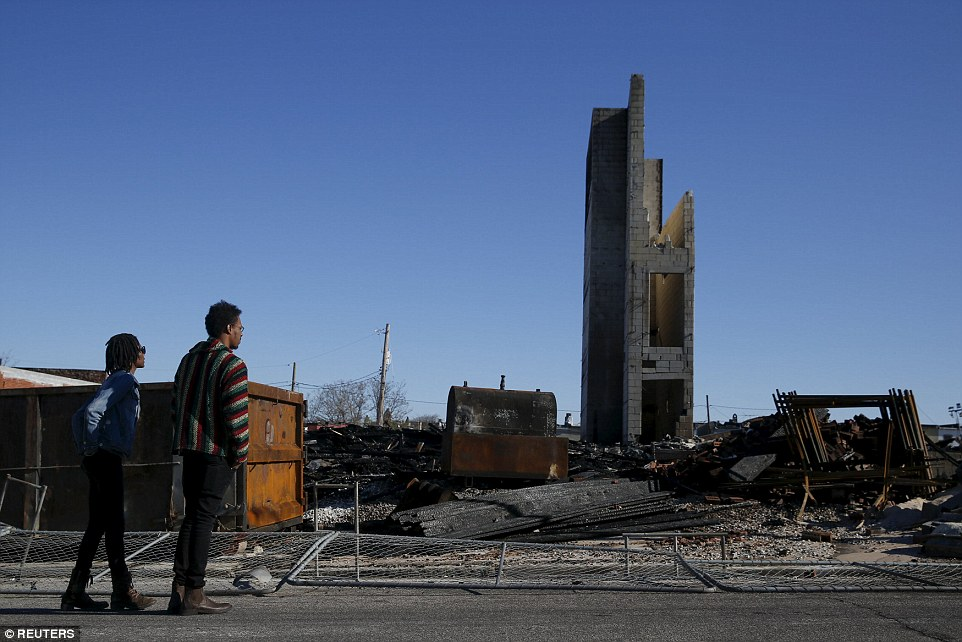 People stand outside the burned community center and apartments across the street from the Southern Baptist Church