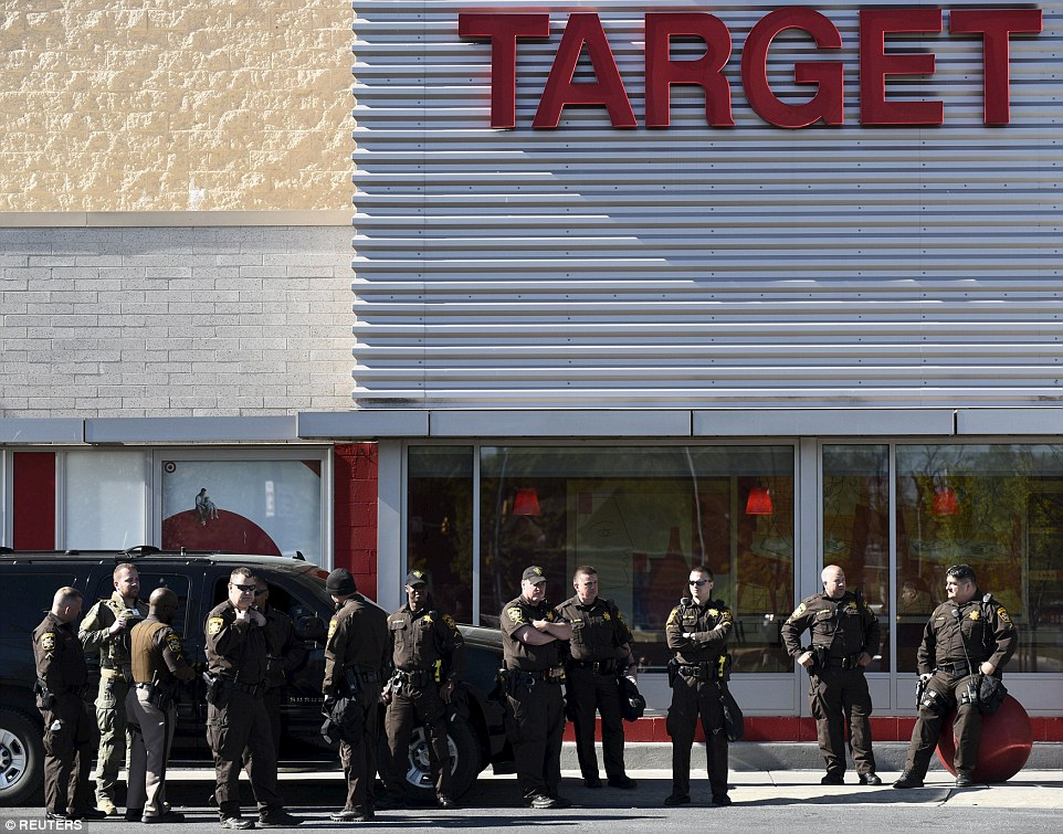 Law enforcement officers with the Charles County Sheriff Department stand guard in front of Target at Mondawmin Mall in Baltimore