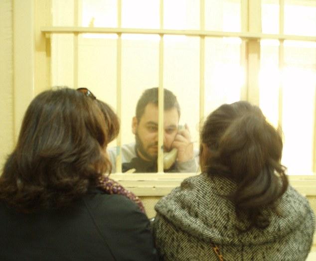 Tras las rejas: Andrew habla con miembros de la familia en un teléfono en la prisión de Korydallos