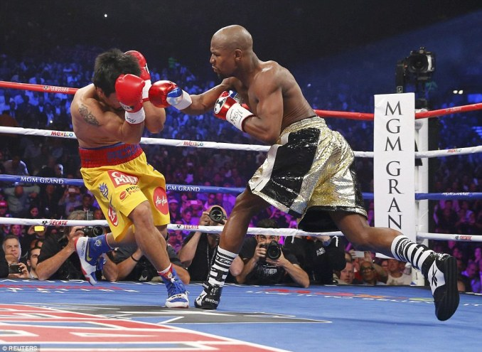 Pacquiao covers his face as Mayweather smells blood and tries to follow up