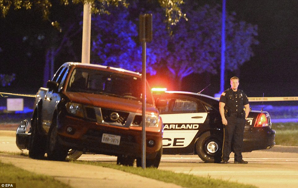A police officer stands next to the pickup truck riddled with bullet holes outside the Curtis Culwell Center in Garland, Texas. Two suspects were shot dead after opening fire near the 'Draw Muhammad' event