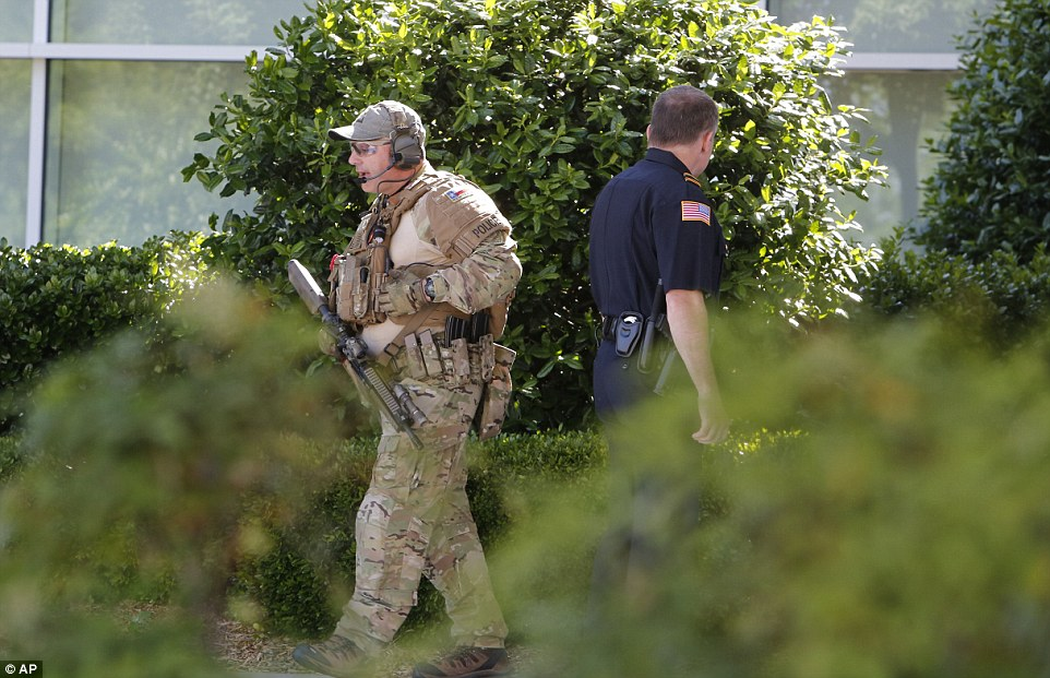 An officer carrying an assault rifle walks around the perimeter of the Curtis Culwell Center as the investigation into the shooting begins