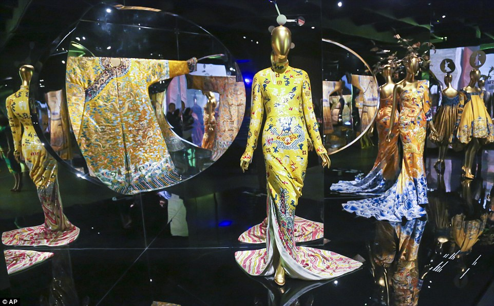 The show: Designs from Yves Saint Laurent, left, Lawrence Xu, center, and John Galliano, right, on display at the Metropolitan Museum's Costume Institute exhibition China: Through the Looking Glass