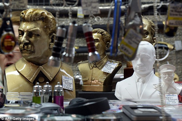 Historians believe that an increasingly positive view of former Soviet Union leader Joseph Stalin (his figurine, left) in Russia is partly driven by the country's current leaders, including President Vladimir Putin (right)