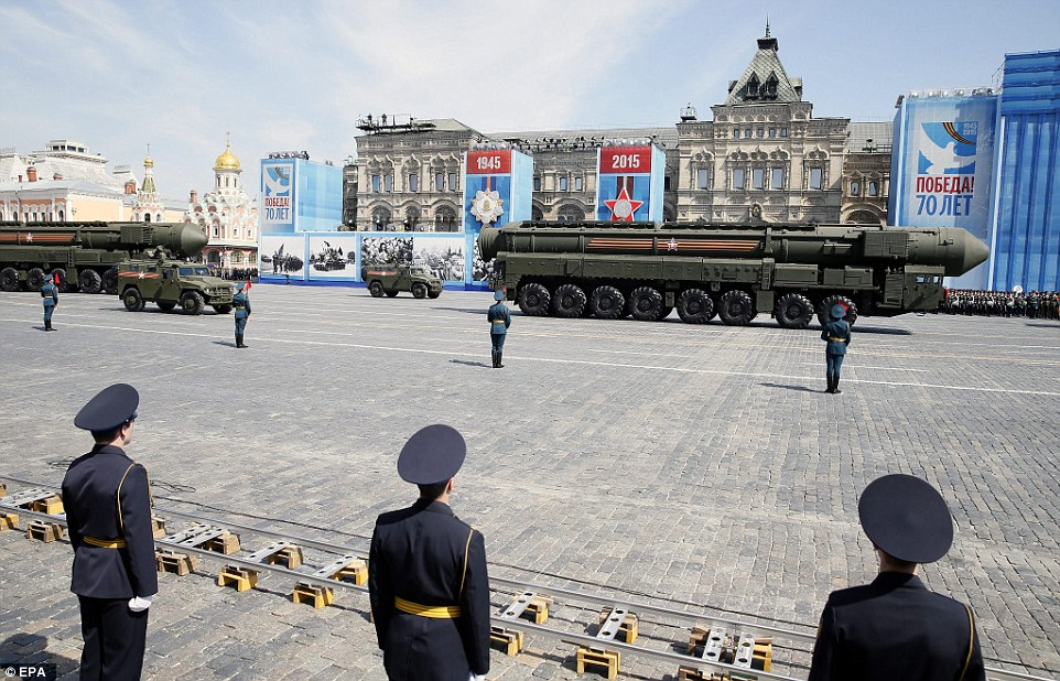 A Russian strategic ballistic missile RS-24 Yars launching vehicle is watched on by serviceman as it moves through Red Square
