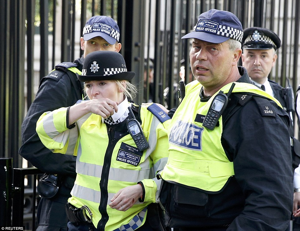An injured female police officer was helped by colleagues away from the fray outside the Downing Street gates