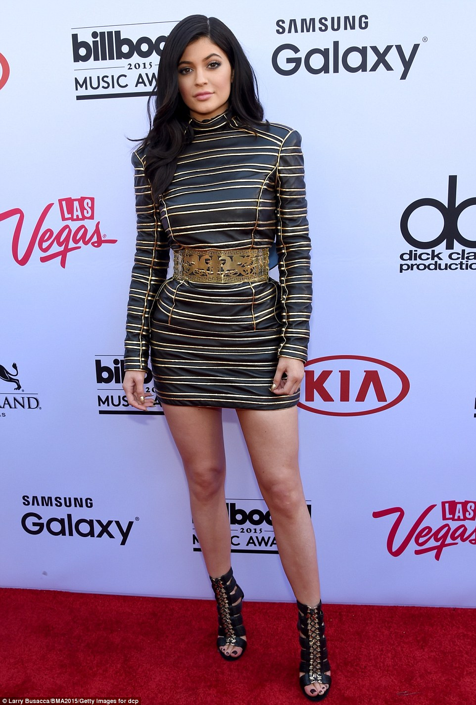 The lips look smaller! 17-year-old Kylie cinched her tiny waist with a gold belt, and rocked a leggy striped mini-dress with gladiator heels