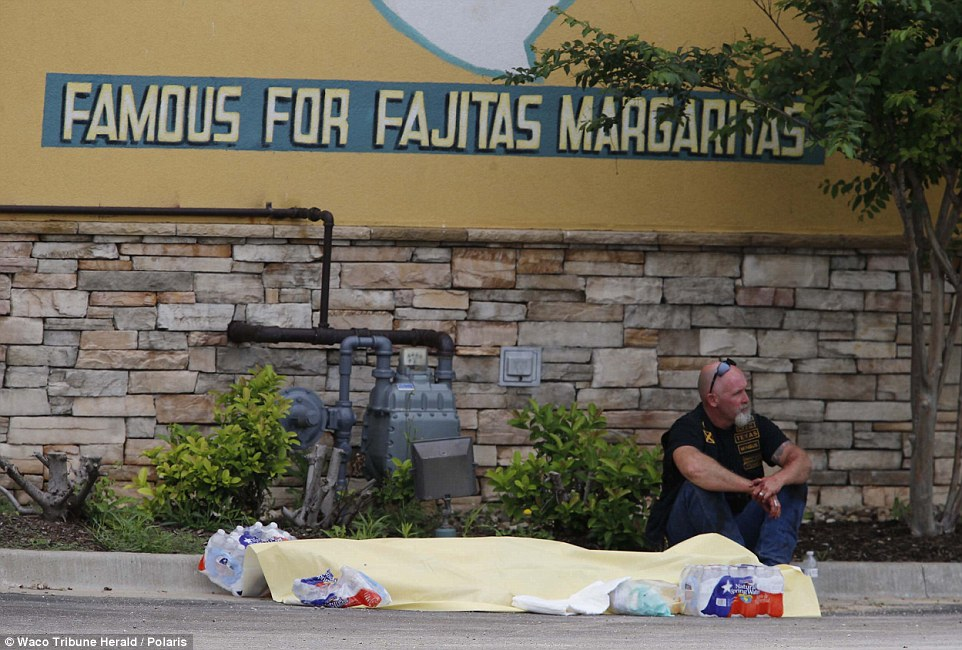 A biker sits next to what appears to be a covered body after several people were killed during the shoot-out