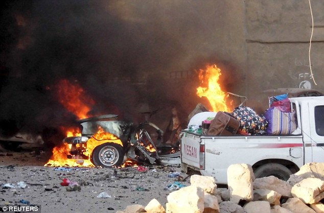Carnage: ISIS  have taken full control of the Iraqi city of Ramadi after security forces fled the area following a series of suicide car bombings. Pictured: A car is engulfed in flames during clashes in the city