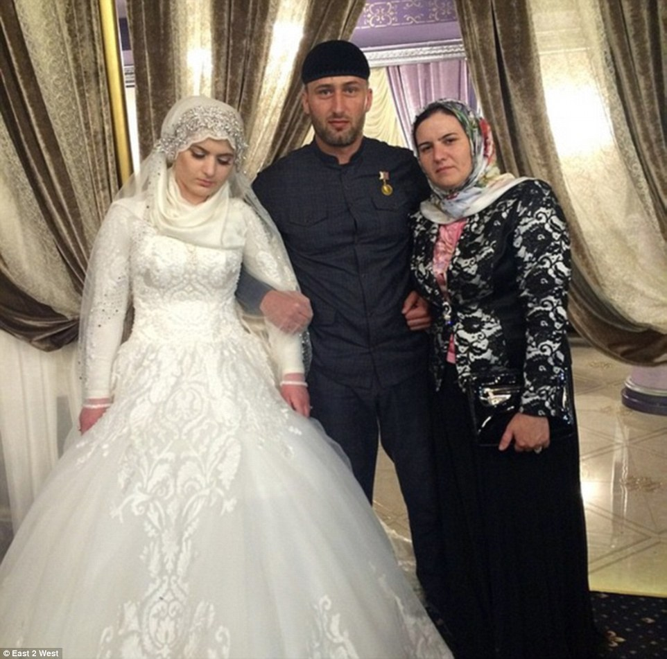 A Chechen police officer poses with Nazhud Guchigov's new wife (left) and his first wife (right)