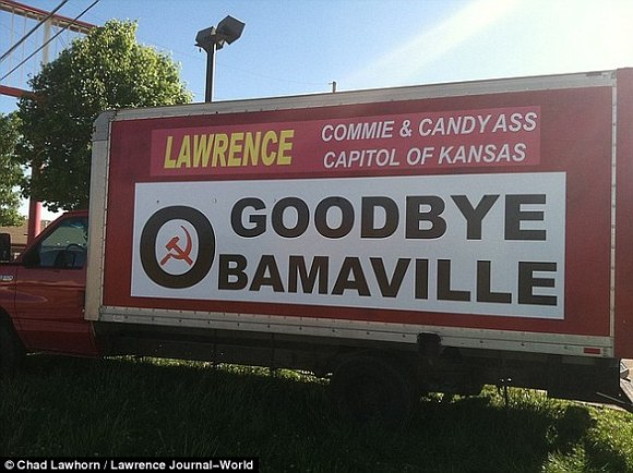 Go big:The main sign reads; 'Lawrence: Commie and Candy Ass Capitol [ sic ] of Kansas. Goodbye Obamaville' (above)