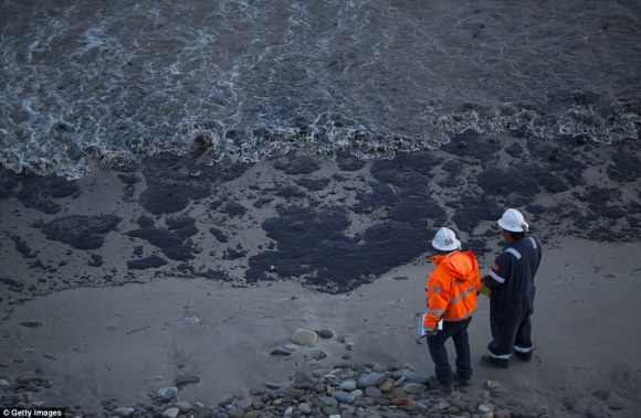 Officials walked along an the oil-covered beach north of Goleta, California