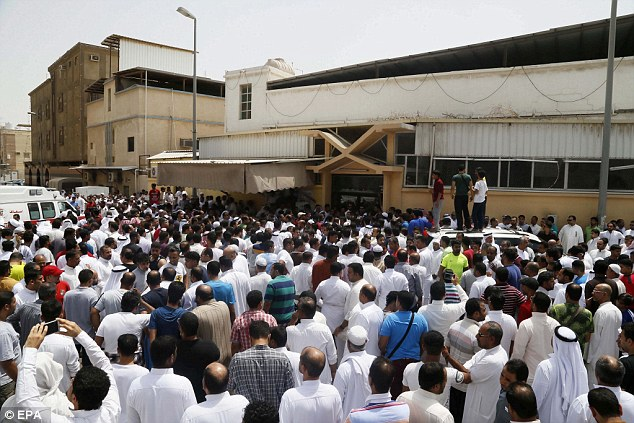 People gather around an ambulance following a suicide attack on the Shi'ite Imam Ali mosque in Saudi Arabia