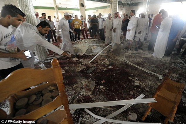 Horror: Saudi men gather around debris following a blast inside a mosque, in the mainly Shi'ite Saudi Gulf coastal town of Qatif, 400 kms east of Riyadh