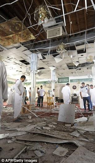 Saudi men gather around debris following a blast inside a mosque, in the mainly Shiite Saudi Gulf coastal town of Qatif, 400 kms east of Riyadh