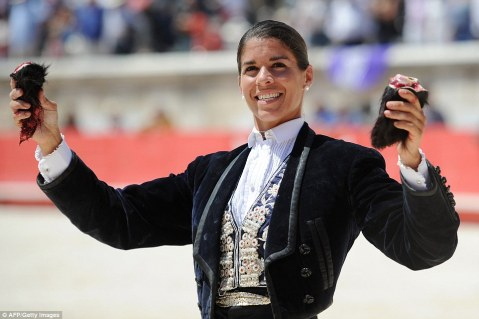 Matador Lea Vicens, 30, holds up the ears of a bull to the delight of the crowd at the Feria de Nimes festival in southern France