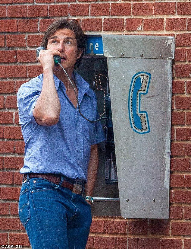 Set in the 1980s: The 52-year-old action star's costume was getting soaked as he pretended to have a tense conversation on an old-fashioned phone booth