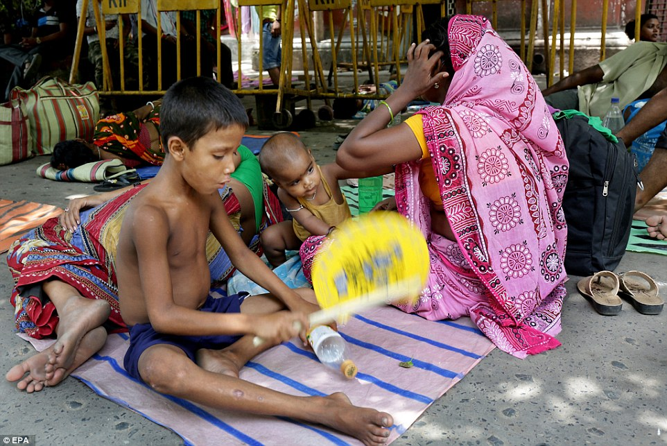 An Indian family wait for treatment at a medical college hospital while temperatures reach 41 degrees Celsius in Calcutta, India