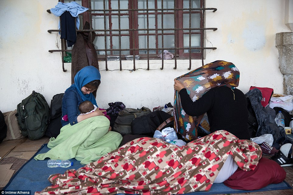 Nowhere to go:Two young migrant mothers breastfeed their babies outside Kos police station. Holidaymakers have complained some migrants sit outside restaurants watching them eat