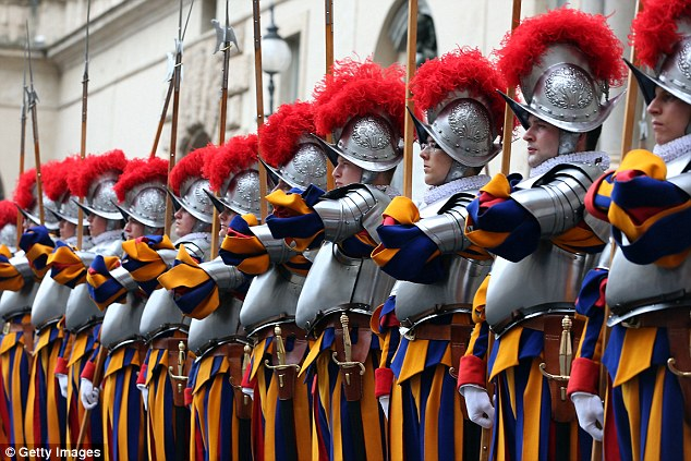 Pope's army: The Pontifical Swiss Guard have protected heads of the Catholic Church since the 1400s. Pictured above are a raft of new recruits joining the militia earlier this month. They still use medieval weapons like swords and halberds, though they are also trained with firearms and modern techniques