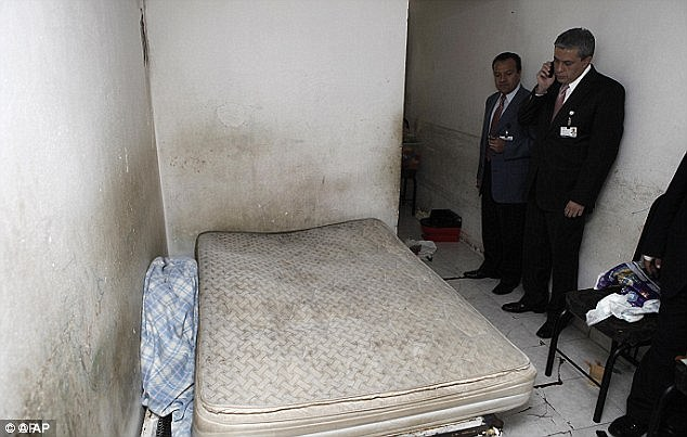 Prison hell: Police investigators stand by the filthy mattress in a room where Jorge Iniestra Salas held two teenage girls captive in Mexico City, fathering five children with one of them