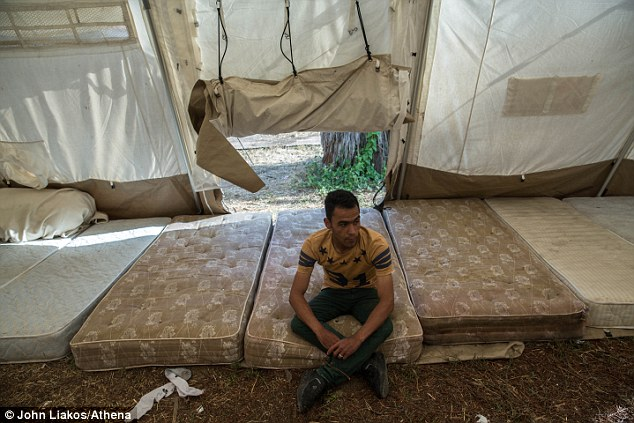 Sleeping rough: A migrant sleeping in a make-shift shelter at the abandoned Elias Hotel on the Greek island