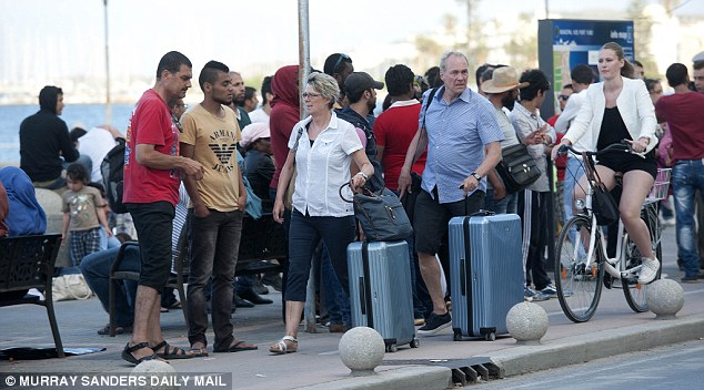 Bemused: Holidaymakers push their luggage through a group of migrants