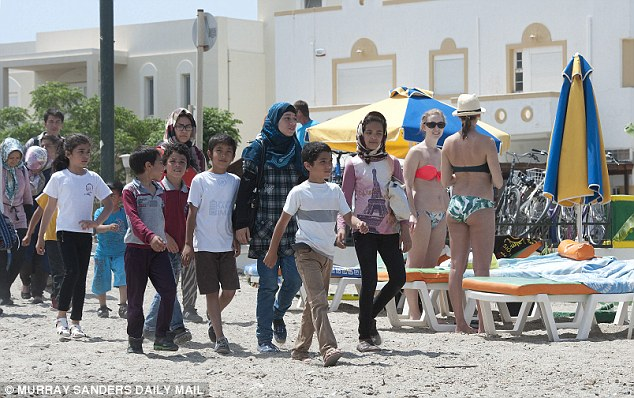 Culture clash: Fully clothed migrants walk past sunbathing tourists in bikinis