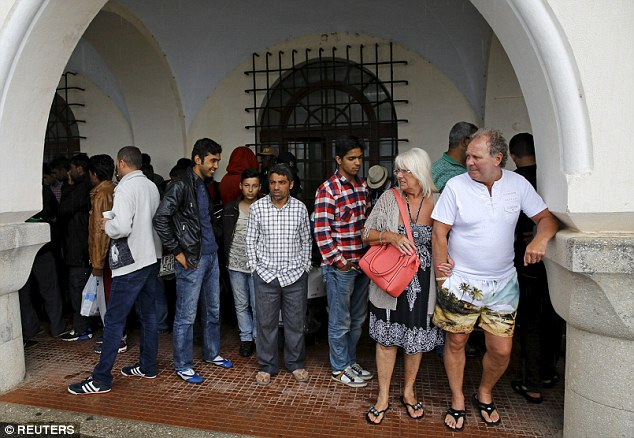 Uncomfortable: A tourist couple (right) and a group of temporarily detained immigrants take shelter from rain outside a police station in Kos island