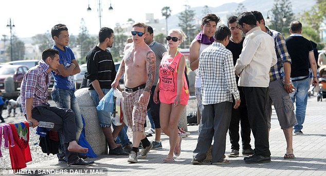 A young British couple make their way through the small Greek island's busy streets which are now awash with migrants