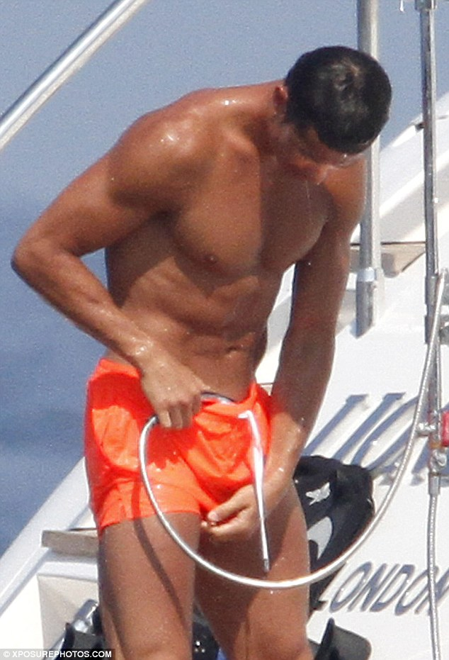 Cooling off: Football hunk Cristiano Ronaldo was giving himself a quick hose down aboard his St Tropez party yacht on Monday