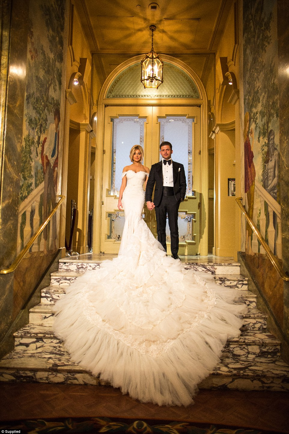 The couple wed in a grand city venue with high ceilings, trompe l'oeil paintings, gilt-edged mouldings and antique chandeliers