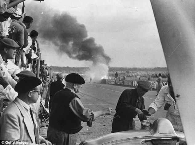 Los mecánicos atienden a los vehículos, mientras un coche continúa ardiendo.