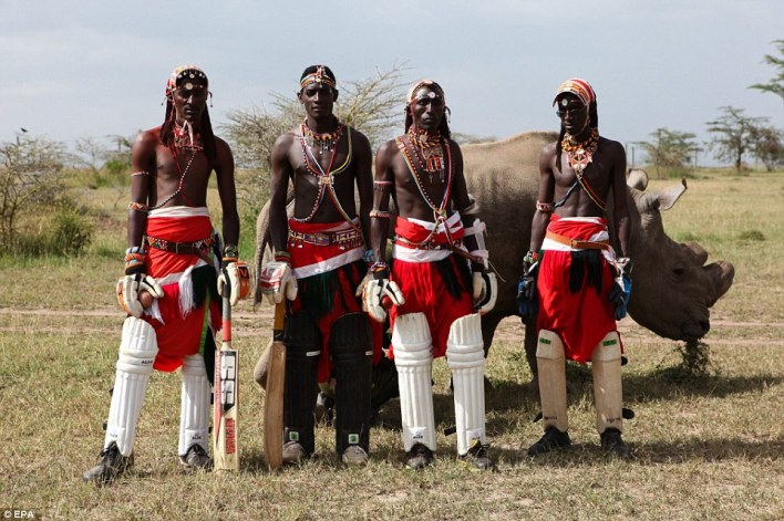 Team photo: Members of the Maasai Cricket Warriors pose for a photo next to Sudan, the last male northern white rhino in the world