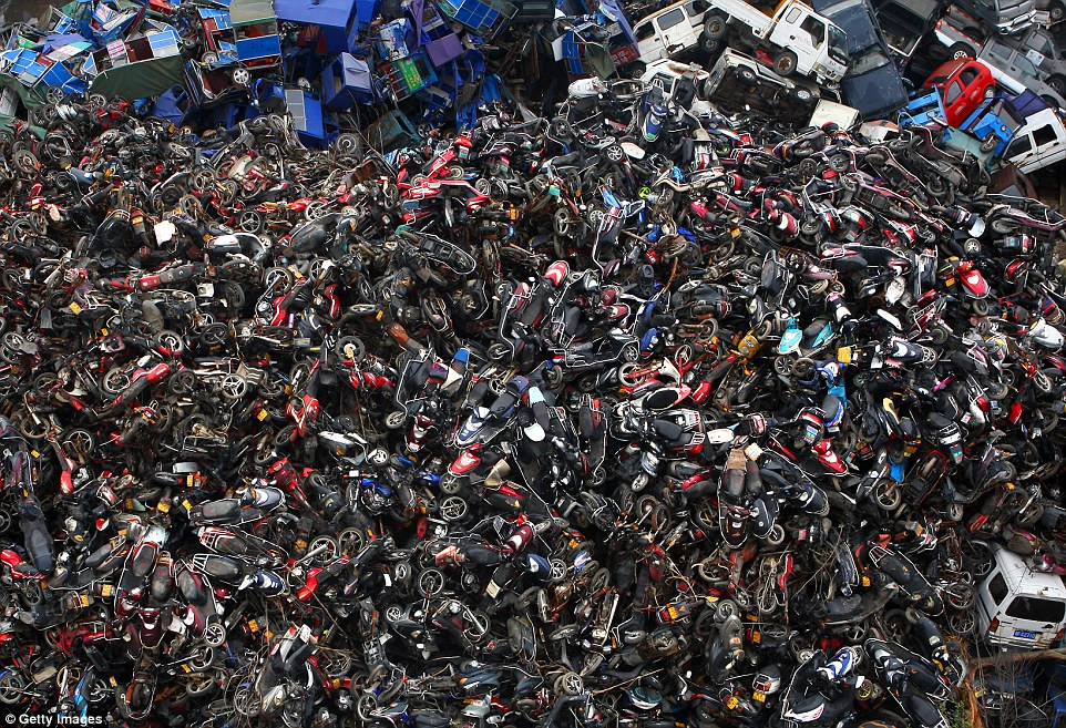 Damaged cars, motor cycles and electric bicycles are seen stacked at a scrapyard in Hangzhou in China