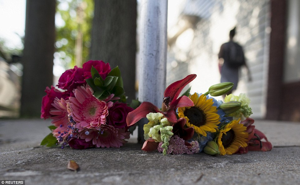 Tribute: Flowers for the victims of Wednesday's shootings, are laid near a police barricade in Charleston, South Carolina, on Thursday