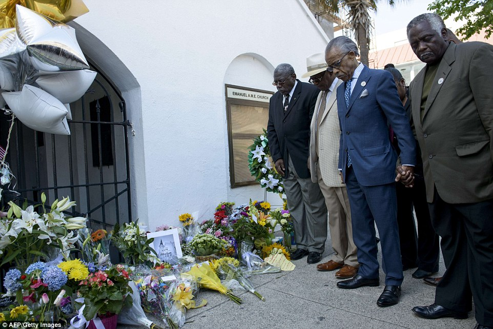 Remembered: The Reverend Al Sharpton and others pray outside the church on Thursday afternoon