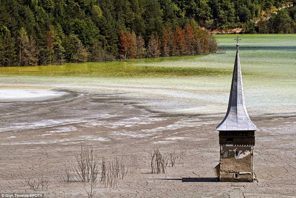 This dramatic image shows what remains of the abandoned village of Geamana in the Apuseni Mountains of Romania. The village was deliberately flooded to form a tailings pond for a vast copper mine and 400 families were evacuated to give the toxic waste somewhere to go. The top of a church tower and a few isolated houses are all that remain sticking out of the contaminated sludge