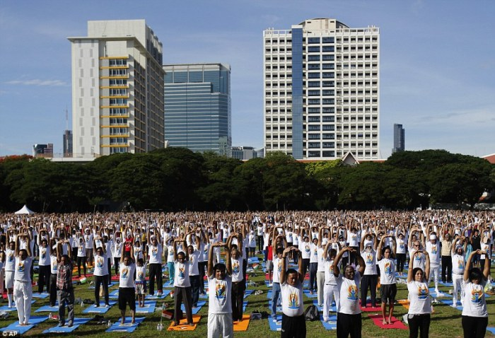 Pictured are a large group participating in a yoga exercise at Chulalongkorn University field, in Bangkok, Thailand