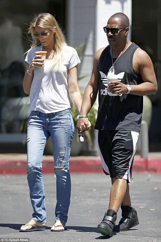 Dressed down: He wore a black Adidas vest with shorts and high top trainers, while his blonde girlfriend was in a white T-shirt and jeans ensemble